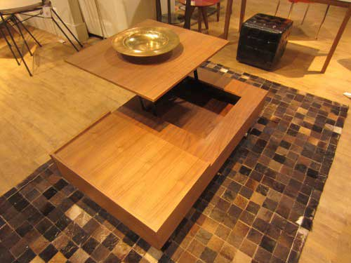 Walnut wood coffee table that has a hinge to allow the top to swivel upward to form a higher table. Transforming furniture.
