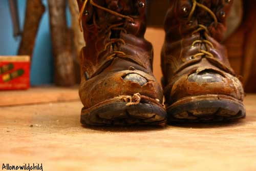 well worn steel toed boots with the steel showing through the toes.