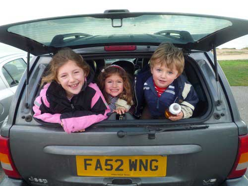 3-kids-in-the-back-of-car-looking-out