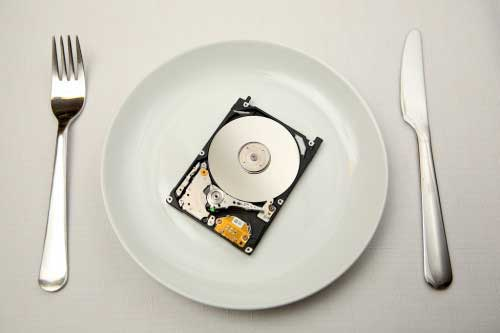 An open hard disk drive on a white plate with a knife and fork... as in consuming technology.