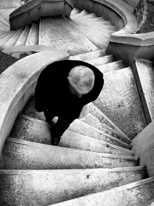 A man is shown from above as he climbs up twisting flights of stairs.