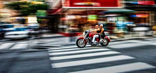 man and woman on a red motorcycle, as they speed through an intersection on a shop filled street.