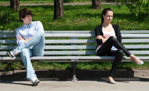 Breaking up. A couple distantly sitting on a bench while not talking.