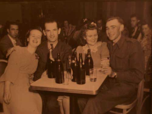 Two couples in the 1940's, wearing suits and dresses, seated at a table with beer bottles on it.