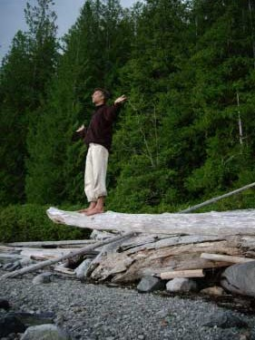 A man balances on a suspended log with bare feet, arms extended, palms raised to the horizon. The BC beach is the background.