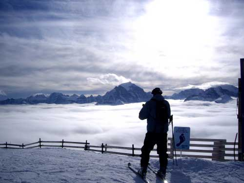 A lone skier is silhouetted overlooking a vast distance to the far mountain range, while standing above the clouds