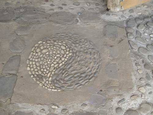 A dusty yin yang symbol made out of dark and light coloured pebbles, set into a concrete floor.