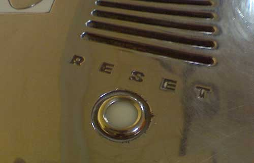 Closeup of reflective surface with reset button inset