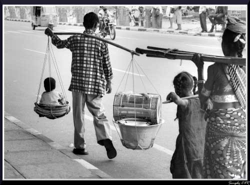 work life balance - an Indian man balancing a large scale with a small child on one side and a silver drum on the other.