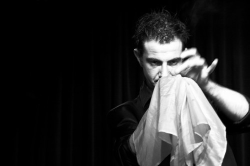 A magician intently focusing on a white handkerchief held in one of his hands.