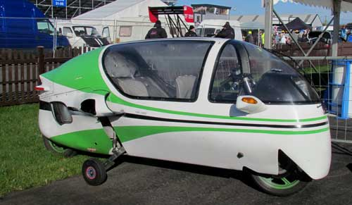 Ecomobile is a covered motorcycle, like a long metal and glass egg.