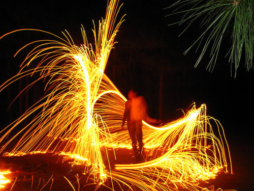 A long exposure in the dark who has danced with a sparkler. It appears that a swirling shower of gold sparks surrounds him.