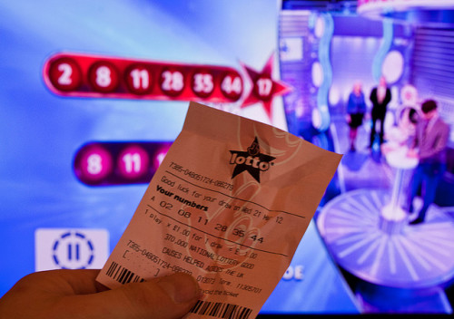 A lottery ticket in a man's hand, comparing to the numbers on the TV screen in the background.