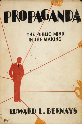 "1928 book cover, ""Propaganda the public mind in the making""with a distant hand pulling strings on a red silhouette of a man."