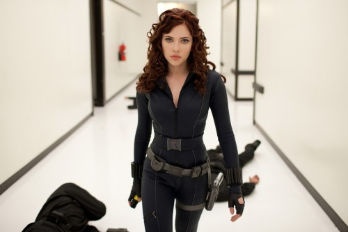 Scarlett Johansson dressed as the Black Widow in a black jumpsuit and gun holster.