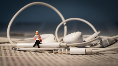 A tiny figure sits on earbuds reading a book, as a depiction of audio books.