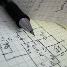 A mechanical pencil rests atop a detailed drawing of a circuit on graph paper.