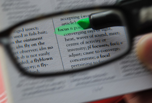 "Minimalism is a focusing tool just like reading glasses; shown here highlighting the word ""focus"" in a book."
