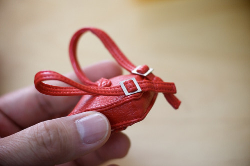 A tiny red leather backpack which is about the size of a human thumb.