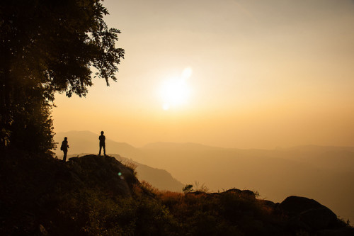 Two silhouetted people look to the distant mountains at sunset. The sky is many shades of pale orange; a monochrome.