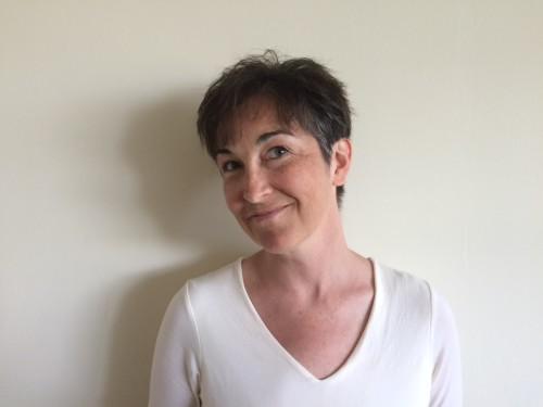 A woman wearing white stands at an angle to show a minimalist no fuss no muss pixie haircut.