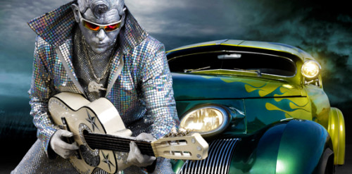 A man imitates Elvis, dressed all in sparkly silver with silver face paint leans on an old car while holding a guitar.