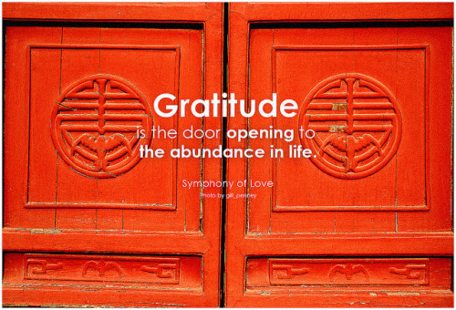 "Gratitude inspires abundance. Two wooden red doors with carved symbols, with the words ""gratitude is the door opening to the abundance in life."