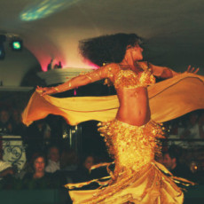 A bellydancer in gold swirls dramatically to the amazement of the audience, with the luxury of space.