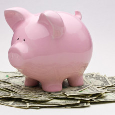 Consider having Less Stuff More Abundance. Pink piggy bank on top of a pile of US one dollar bills