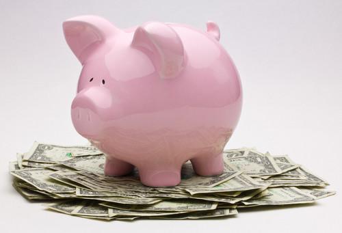 Consider having Less Stuff More Abundance. Pink piggy bank on top of a pile of US one dollar bills