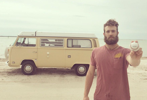 The simple life. Millionaire pitcher Daniel Norris holds a baseball out while standing on the beach in front of the VW van he lives in.
