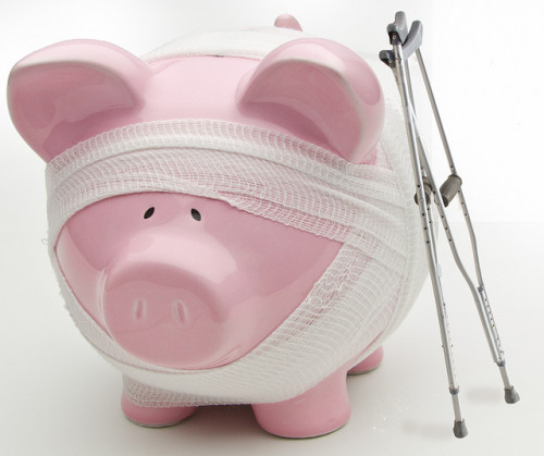 Injured piggy bank with crutches and bandages. Are your savings healthy? If not, consider less stuff more money.