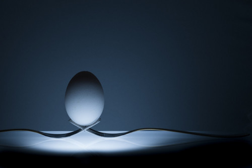 Life lessons are often about balance. An egg perfectly balances on two interlaced forks, sitting on an underlit table.
