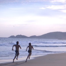 A healthy woman and man sprint along the beach toward the distant mountains. No gear workouts suit a minimalist lifestyle.