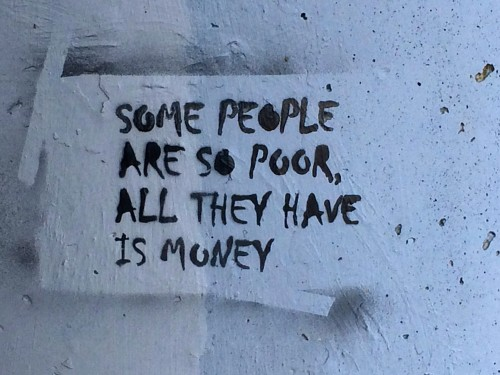 "A message, spray painted on a concrete wall, ""Some people are so poor, all they have is money"""